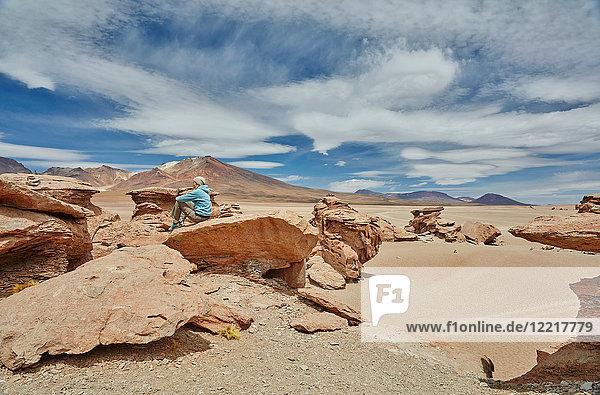 Frau sitzt auf einem Felsen und schaut auf die Aussicht  Villa Alota  Potosi  Bolivien  Südamerika