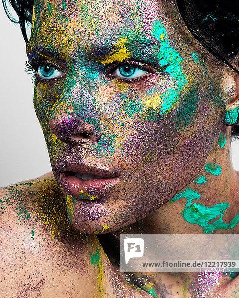 Studioporträt einer blauäugigen jungen Frau mit glitzerndem  mehrfarbigem Puder im Gesicht