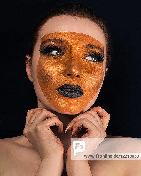 Studioporträt einer jungen Frau mit nackten Schultern  Bronze im Gesicht und schwarzem Lippenstift