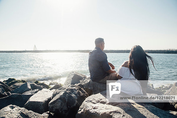 Couple sitting on coastal rocks  looking at view  rear view