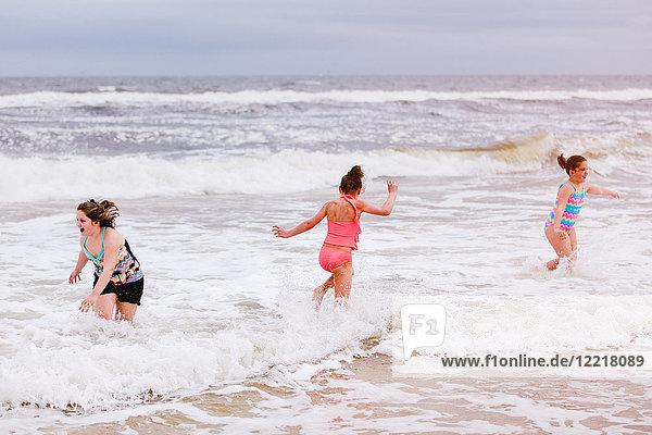 Three girls playing in ocean waves  Dauphin Island  Alabama  USA