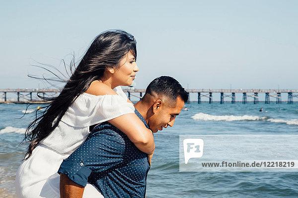 Mann gibt Frau Huckepack am Strand  Seal Beach  Kalifornien  USA
