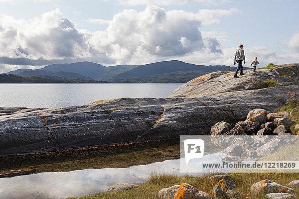Mann und Sohn wandern auf einer Felsformation im Fjord  Aure  More og Romsdal  Norwegen