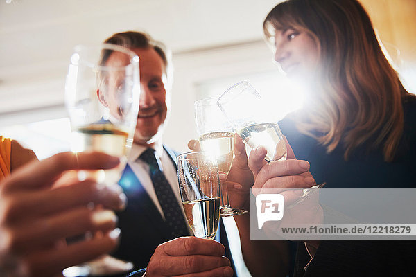 Business team raising champagne toast at office celebration