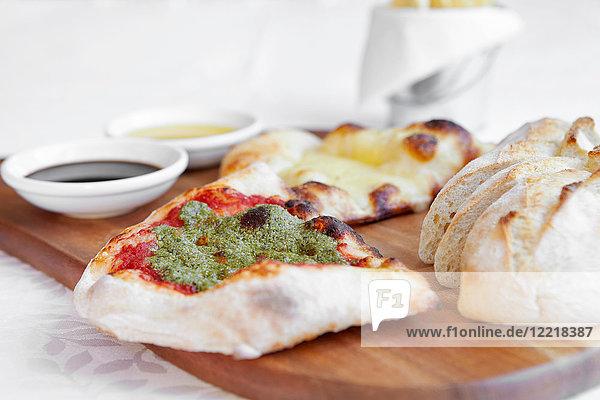 Frisches Pizzabrot mit Dippsaucen auf Schneidebrett