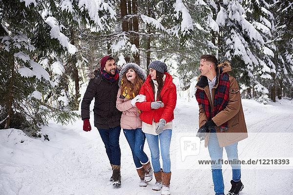 Freunde laufen und lachen im Schnee