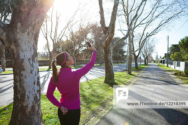 Rear view of woman taking selfie in tree lined street