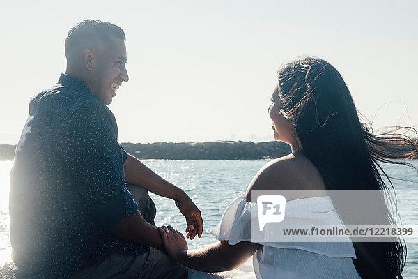 Paar sitzt auf Küstenfelsen  hält Hände und lächelt