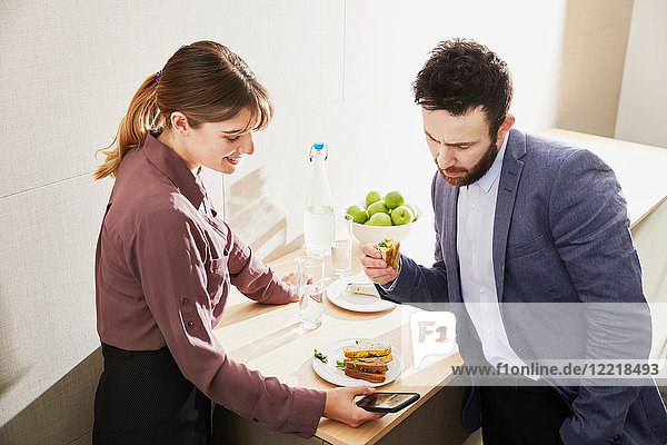 Businesswoman and man looking at smartphone during working lunch