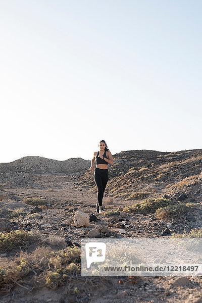 Junge Läuferin läuft auf unbefestigter Strecke in trockener Landschaft,  Las Palmas,  Kanarische Inseln,  Spanien