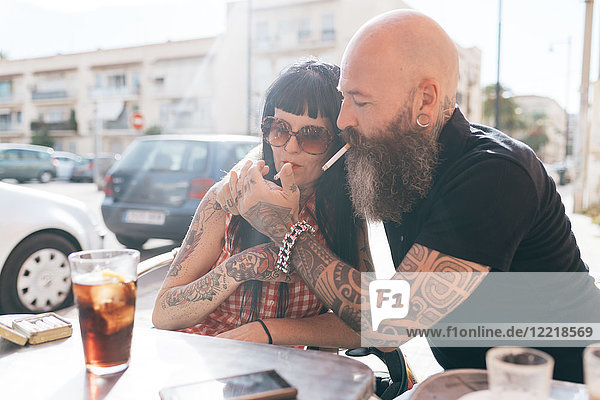 Mature hipster couple lighting cigarette at sidewalk cafe  Valencia  Spain