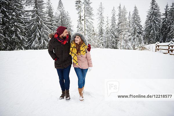 Junges Paar geht im Schnee spazieren