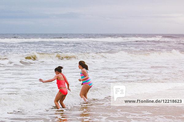 Two girls playing in ocean waves  Dauphin Island  Alabama  USA