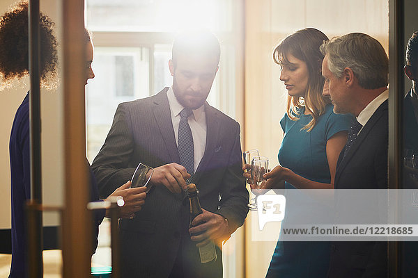 Businessman opening champagne at office celebration