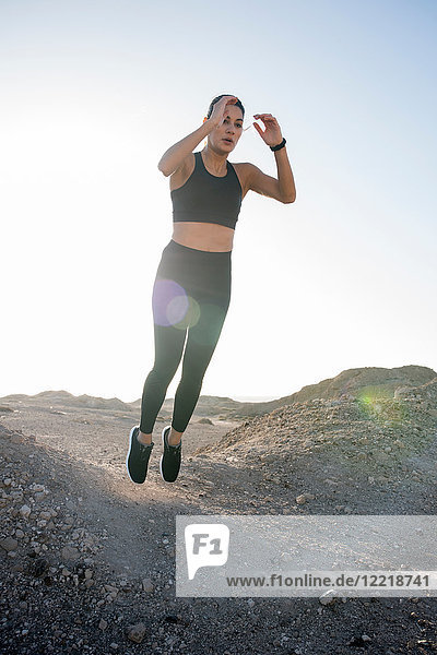 Young female runner jumping mid air in arid landscape