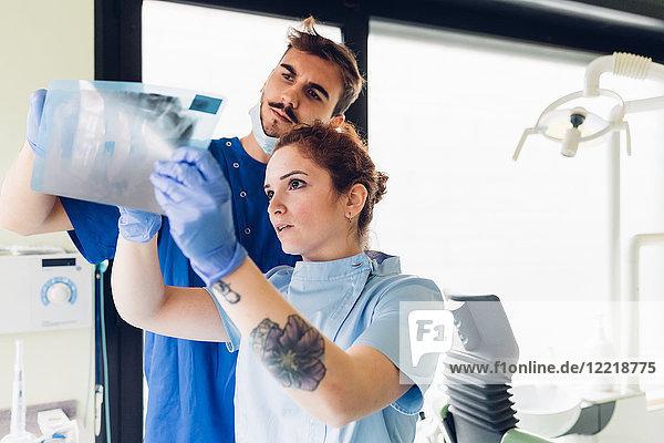 Zwei Zahnärzte in einer Zahnarztpraxis  die sich ein Röntgenbild ansehen