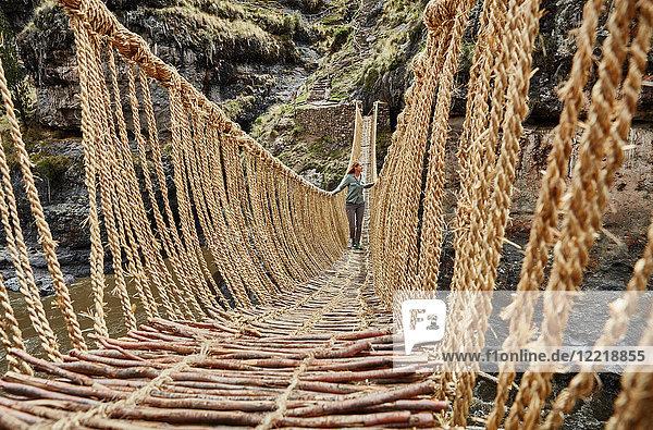 Weibliche Touristin überquert Inka-Seilbrücke  Huinchiri  Cusco  Peru