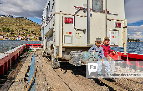 Portrait of two boys sitting at rear of recreational vehicle  on ferry  Tiquina  La Paz  Bolivia  South America