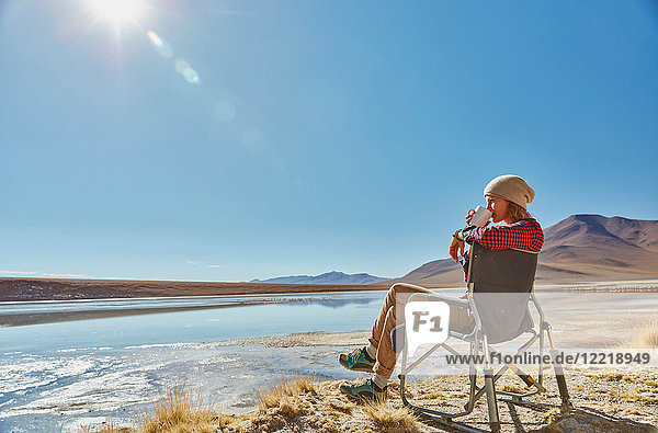 Frau sitzt im Campingstuhl und schaut auf Aussicht  Salar de Chalviri  Chalviri  Oruro  Bolivien  Südamerika