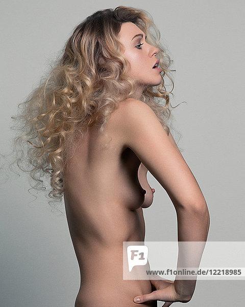 Akt-Atelierporträt einer jungen Frau mit Händen auf dem Bauch  Seitenansicht