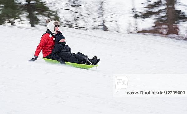 Mutter und Sohn rodeln auf schneebedecktem Hügel