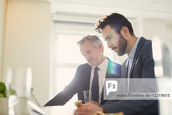 Businessmen looking at laptop over working lunch