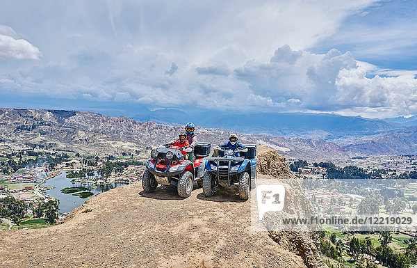 Mother and sons on top of mountain  using quad bikes  La Paz  Bolivia  South America