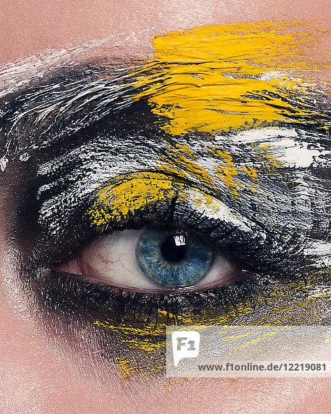 Studioporträt einer blauäugigen Frau mit gemaltem Gesicht  Nahaufnahme des Auges