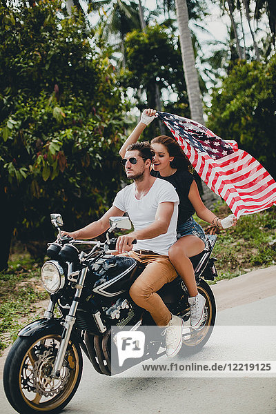 Junges Paar hält die amerikanische Flagge hoch  während es auf einer Landstraße Motorrad fährt  Krabi  Thailand