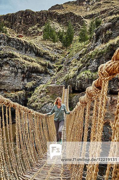 Reife Frau überquert Inka-Seilbrücke  Huinchiri  Cusco  Peru