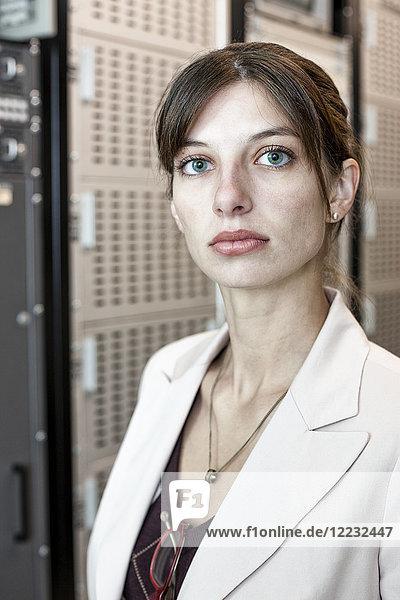 Porträt einer Technikerin  die in einem großen Computer-Serverraum arbeitet.