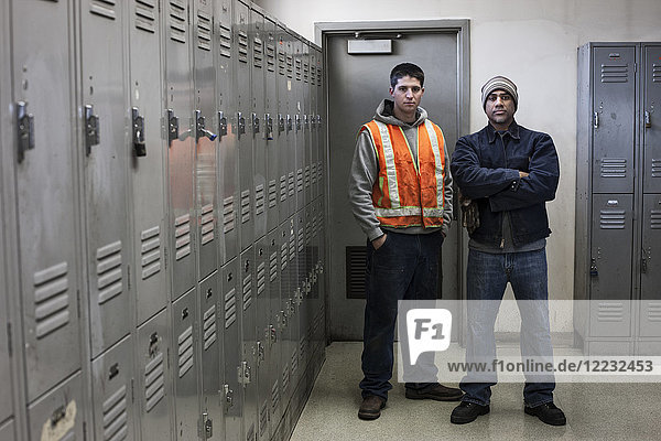 Junger kaukasischer Mann und ein schwarzer Fabrikarbeiter stehen neben Schließfächern in einem Pausenraum der Fabrik