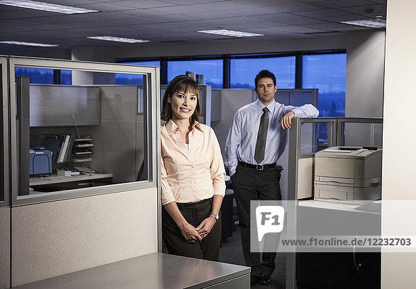 Zwei junge Geschäftsleute arbeiten bis in den Abend hinein in einem Zellenbüro  das eingerichtet wurde.