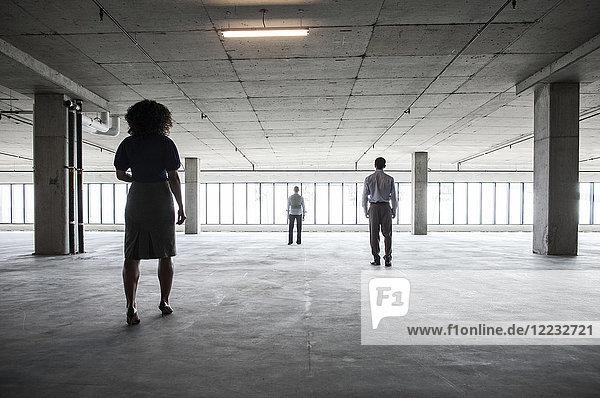 Geschäftsleute gehen in einem großen  leeren Büroraum auf die Fenster zu.