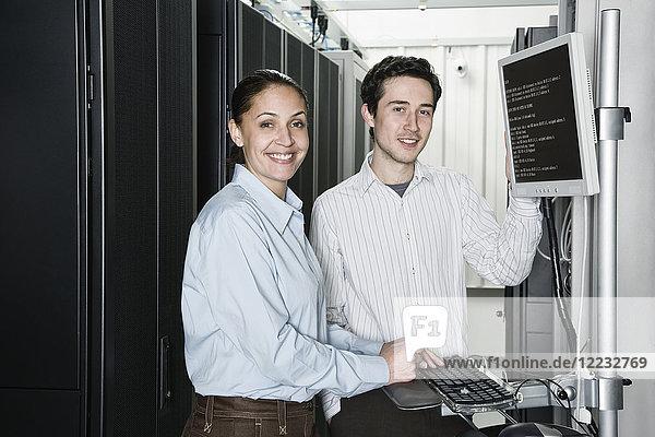 Kaukasische Computertechniker und -technikerinnen  die Daten auf Computerservern in einer Computer-Serverfarm überprüfen.