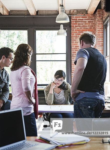 Mixed race group of people meeting to brainstorm an issue in a creative office.