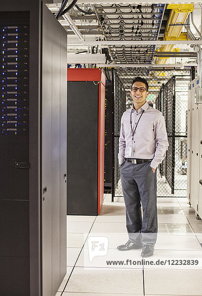 Kaukasischer Techniker  der mit Computerservern in einer Computerserverfarm arbeitet.