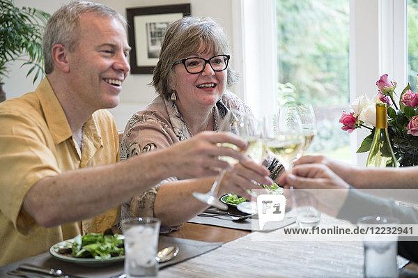 Seniorenpaare stoßen auf eine Dinnerparty zu Hause mit Gläsern Weißwein an.