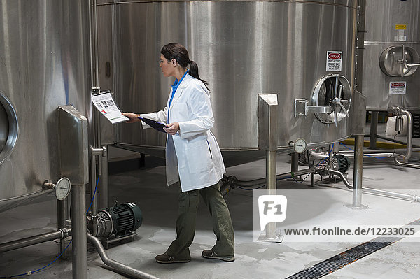 Caucasian female technician checking large stainless steel processing tanks in a bottling plant. that makes flavoured bottled water.