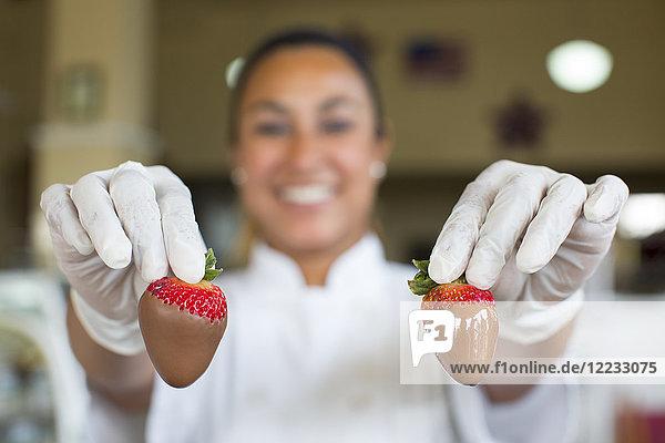 Hispanische Frau  die in einem Süßwarengeschäft eine schokoladenüberzogene Erdbeere in der Hand hält.