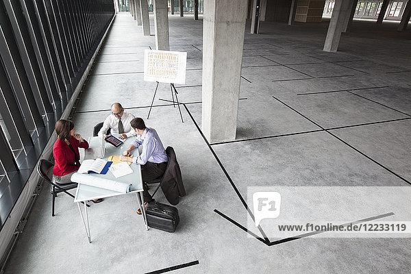 Asiatischer Architekt mit einem kaukasischen Mann und einer kaukasischen Frau bei der Planung des Arbeitsplatzes in einem neuen rohen Bürogebäude.