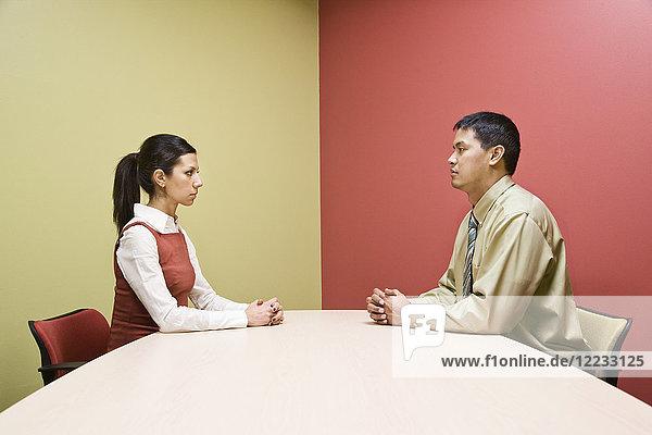 Geschäftsmann und -frau sitzen an gegenüberliegenden Seiten eines Konferenztisches in einem sehr farbenfrohen Raum.