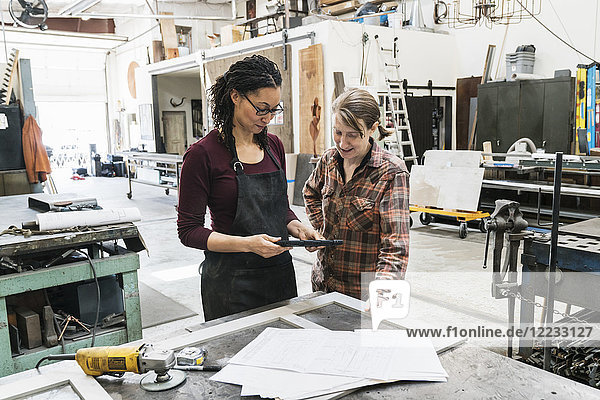 Two women standing at workbench in metal workshop  holding digital tablet.