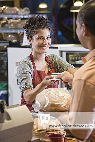 Kaukasische Frau an der Kasse einer Bäckerei  die mit einem Kunden eine Kreditkartentransaktion durchführt.