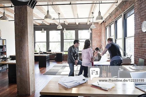 Eine gemischtrassige Gruppe von Leuten trifft sich zum Brainstorming eines Themas in einem kreativen Büro.