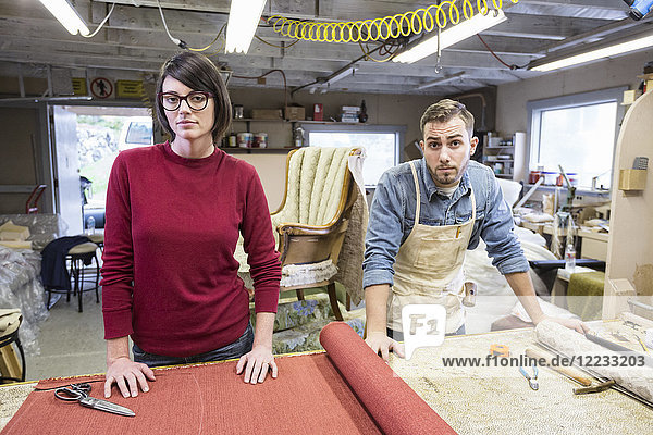 Ein junges kaukasisches Ehepaar arbeitet als Team von Polsterern an einem Stuhl.