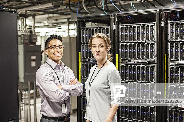 Kaukasische Techniker und Technikerinnen in einer großen Computer-Server-Farm.