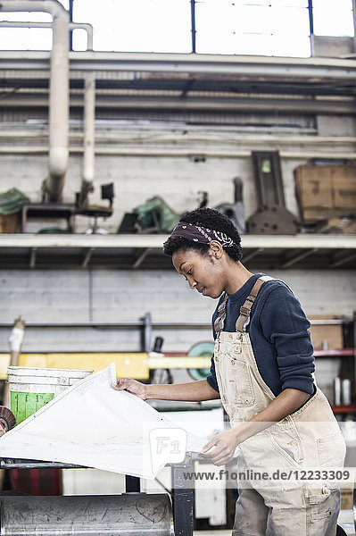 Black woman factory worker going over project plans in a sheet metal factory.