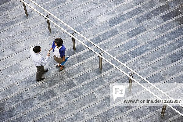 Blick von oben auf eine Geschäftsfrau und einen Geschäftsmann  die auf Stufen hinauf zu einem großen Bürogebäude stehen.