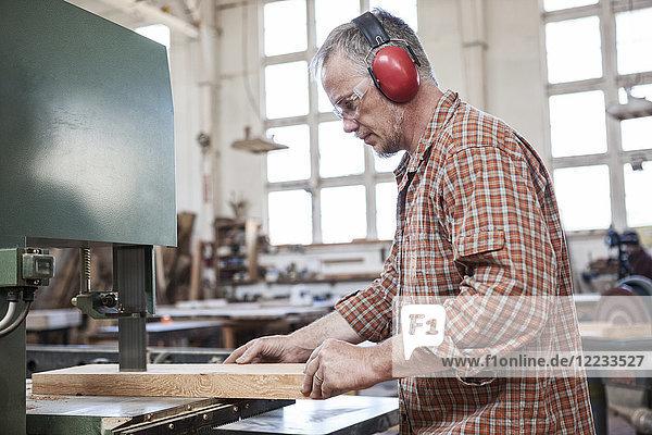 Kaukasischer Fabrikarbeiter  der in einer holzverarbeitenden Fabrik Holz mit einer Bandsäge schneidet.